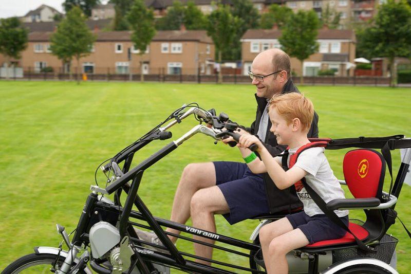 Man and boy on electric bike.