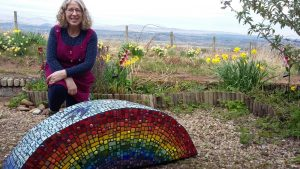 Local mosaic artist JudyJamJar with her latest creation, a giant rainbow inspired by the rainbow paintings made by the children in the village of Kippen. It sits in her front garden to be enjoyed by anyone walking past.